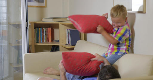 Son and dad fighting with pillows at home Footage
