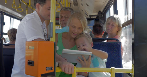 Family entertaining with tablet PC in the bus Footage