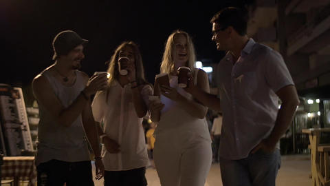 Friends toasting with coffee cups in night street Footage