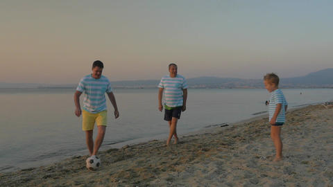 Family football team playing at the seaside Footage