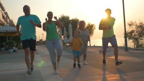 Happy family finishing evening run on resort Footage