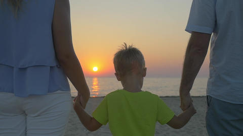 Family with child looking at sunset over sea Footage