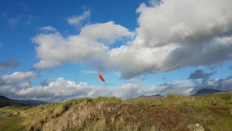 Walking towards a red flag, sand dunes and mountains Live Action