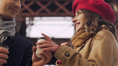 Man giving a cup of coffee to his girlfriend, trying to warm in cold weather Footage