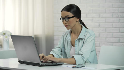 Young asian woman typing on laptop, writing flirty message on dating website Live Action