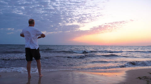 Adult sportsman warming up arms on seashore in the morning GIF