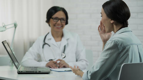 Physician informing patient about good news, showing test results on laptop Live Action