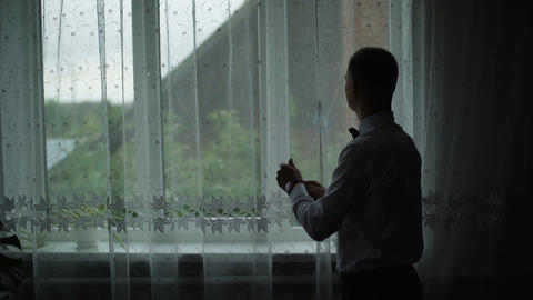 Young man admire view from window at home and put on a shirt. Slow motion Archivo
