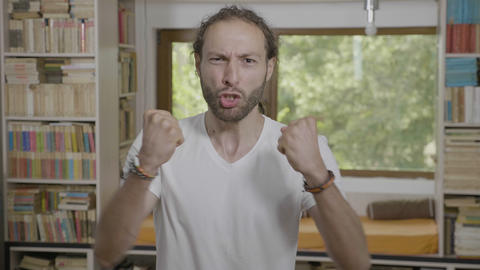 Portrait of excited motivated millennial man screaming and pumping fists Footage