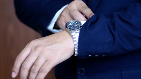 Businessman in suit checking the time on wrist watch.Waits. Looks at the clock, Footage