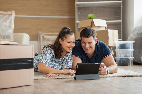 Couple planning decoration on line with a tablet and moving home in the living Photo