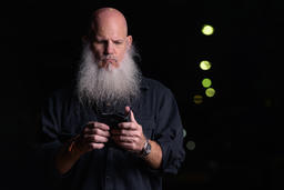 Portrait Of Bald Man With Beard Using Mobile Phone Outdoors At Night フォト