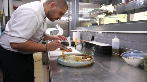 Cook in restaurant kitchen placing pieces of grilled meat Archivo