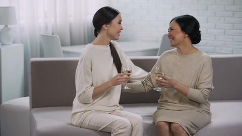Two happy asian women drinking white wine, celebration of victory, partnership Footage