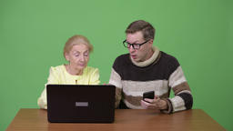 Tired senior businesswoman using laptop and upset young man using phone Footage