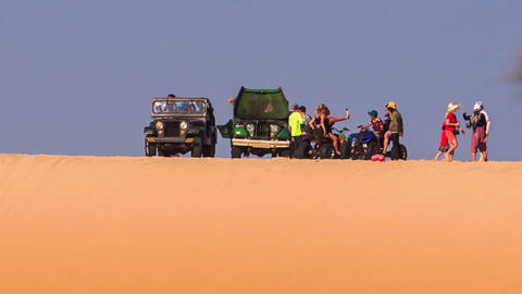 Tourists Walk around Jeeps Quads on Sand Dune Crest on Skyline Footage