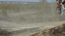slow motion group of motorcyclists jumping a mountain, dirt road Footage
