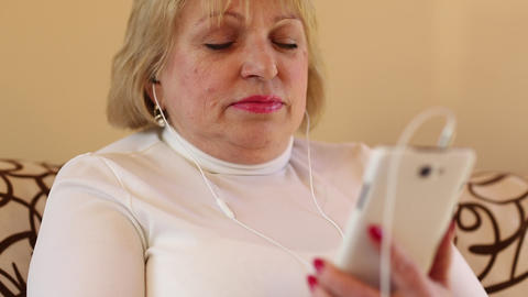 Blonde woman with with closed eyes sits on the sofa and listens to music Footage