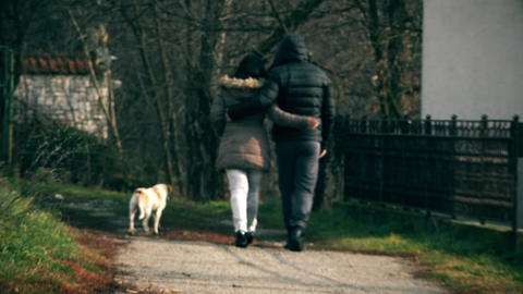 A Girl and a Guy Embraced walk the Street with a Dog Footage