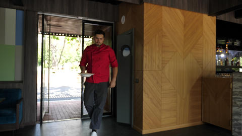 Chief exiting the kitchen with a plate in hands Footage