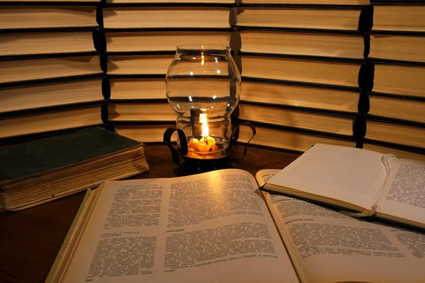 Book and candle on the table on the background of old books Fotografía