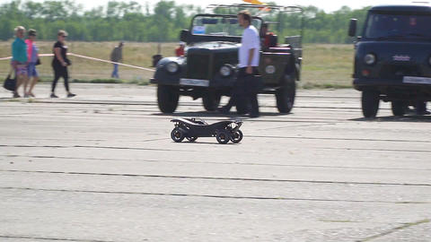 Black radio-controlled model of a car drives fast in the park ビデオ