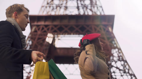 Rich lady doing shopping in Paris forcing her boyfriend to carry her purchases Live Action