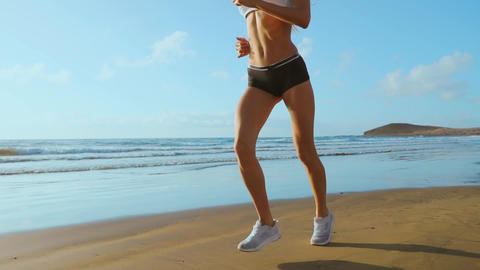 Beautiful sporty women in white sneakers running along a beautiful sandy beach Footage