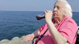 Senior woman in a wheelchair is drinking soft drinks by the sea Footage