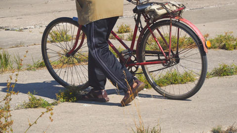 Elderly man walking down the street with old Bicycle 영상물