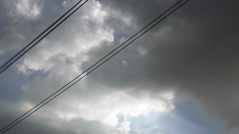 Gray overcast clouds on blue sky before rain or storm. Power lines in the sky GIF