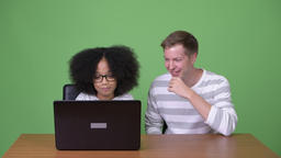 Young African girl and young Scandinavian man using laptop together Footage