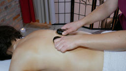 Woman is receiving a hot stones massage Footage