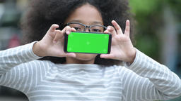 Young cute African girl with Afro hair showing phone in the streets outdoors Footage