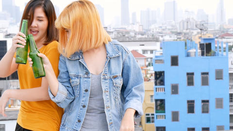 Young Asian woman lesbian couple dancing and clinking bottles of beer party on rooftop Live Action