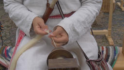 Woman is spinning wool on a spinning wheel ビデオ