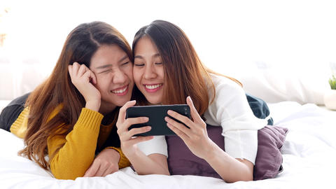 Young asian lesbian couple selfie on smartphone on bed room at home Footage