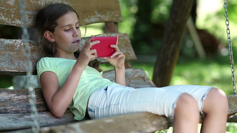 Beautiful girl with red smartphone sits on the swing bench in garden Footage