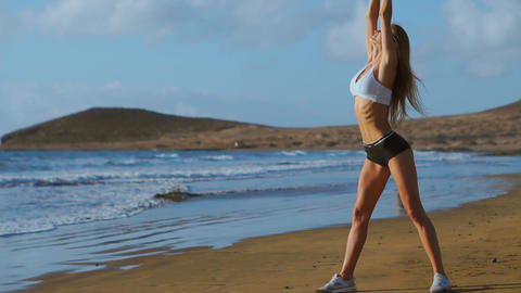 Woman stretching legs and hamstrings doing Standing Forward Bend Yoga stretch Live Action