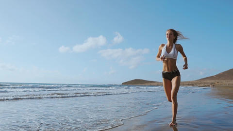 Healthy woman running on the beach, girl doing sport outdoor, happy female Live Action