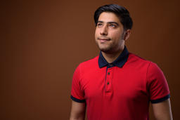 Studio shot of young handsome Iranian man against brown backgrou Photo