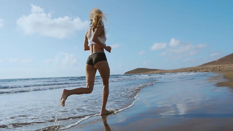 Running woman, female runner jogging during outdoor workout on beach., fitness Footage