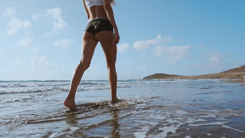 Woman bare foot walking on the summer beach. close up leg of young woman walking Live Action