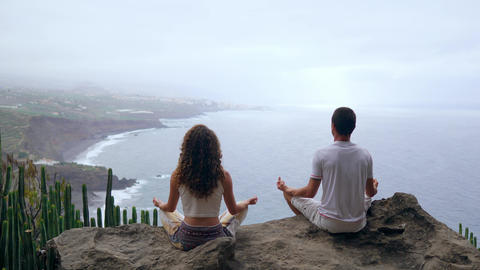 A man and a woman sitting on top of a mountain looking at the ocean sitting on a Footage