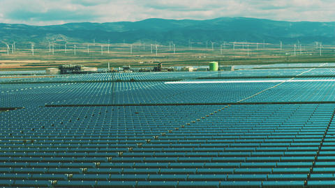 Renewable energy generation. Aerail view of solar power station and wind Live Action