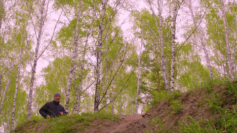 Sportive man waving and running on hill with birch trees GIF