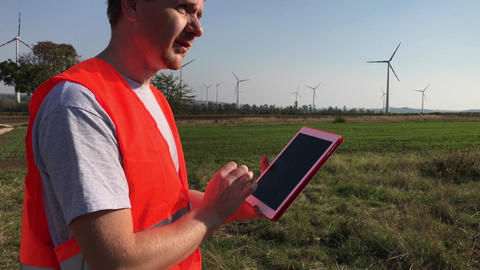 Engineer looks at tablet and to wind turbine towers Footage