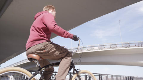 young man rides bicycle along track under modern bridges 영상물