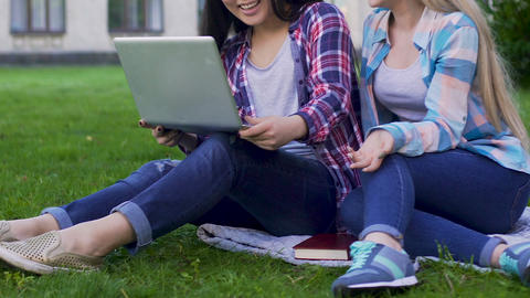 Two female students on lawn holding laptop and having discussion, friendship Live Action