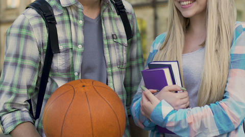 Guy with basketball ball talking to girl with books, popular guy and nerd, flirt Footage